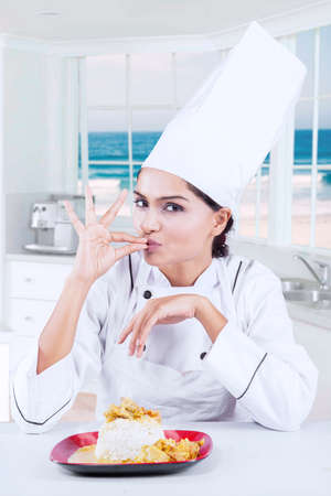 indian cookery: Image of young female chef giving a perfect gesture with hand for delicious food while looking at the camera in the kitchen