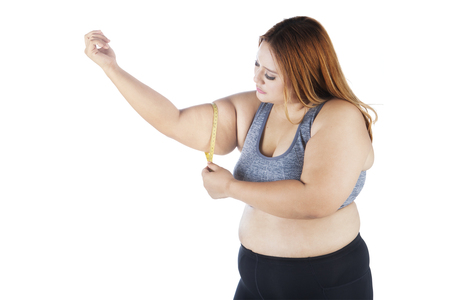 obeso: Portrait of overweight young woman measuring her biceps, isolated on white background Foto de archivo