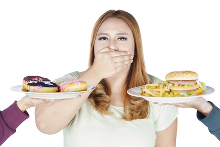 offered: Portrait of obese woman refusing fast food offered while closed her mouth, isolated on white background Stock Photo