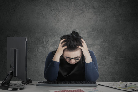 dizzy: Businesswoman holding her head on the desk while feeling dizzy with financial crisis Stock Photo