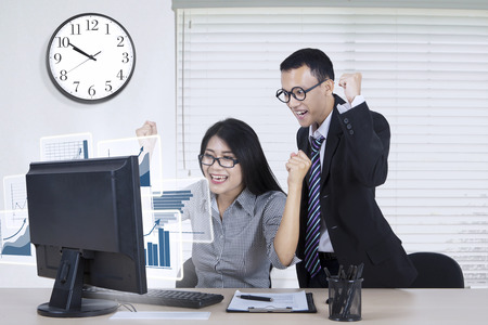 profit celebration: Two happy business team looking at financial chart on the computer monitor and expressing their success