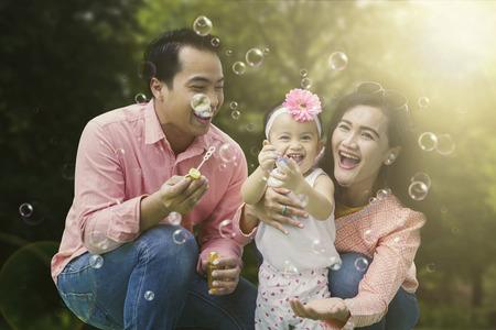 Portret van vrolijke familie spelen met zeepbellen terwijl ze samen in het park lachen Stockfoto