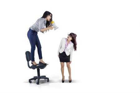 Foto de la joven empresario gritando a su subordinado mediante el uso de un megáfono, aislado en fondo blanco