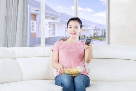 changing channels: Photo of a pretty woman watching television on the sofa while eating popcorn and holding a remote control