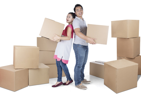 Full length of young woman and man carrying box while standing in the studio, isolated on white background Stock Photo