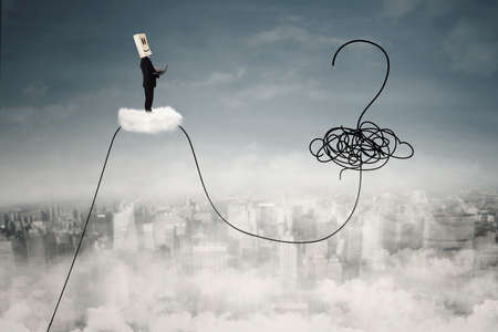 Image of a businessperson with laptop and cardboard head standing on the cloud with question mark at the sky Stock Photo