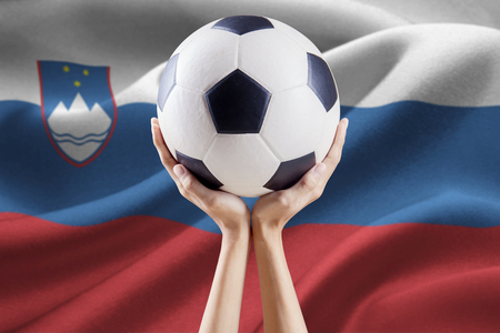 Image of two arms holding a soccer ball with national flag background of Slovenia Stock Photo