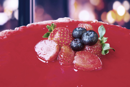 jello: Close up of fresh strawberry and blueberry above delicious cake for dessert with light bokeh background