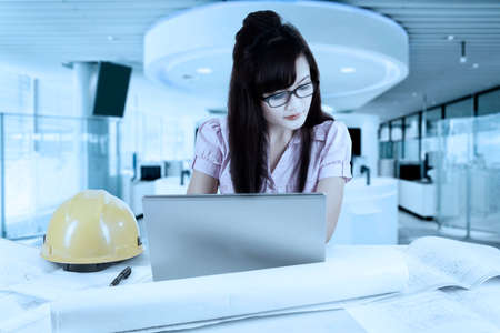 asian architect: Portrait of an attractive Asian architect working in the office with laptop and blueprint on the table