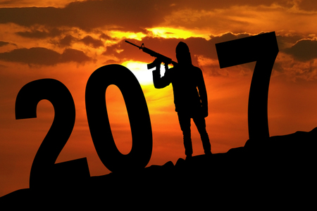 Silhouette of male terrorist carrying guns while terrorizing the new year with numbers 2017 on the hill Stock Photo