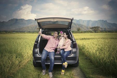 田んぼでスマート フォンを使用して selfie を撮影しながら、車の後ろに座っている幸せな家族
