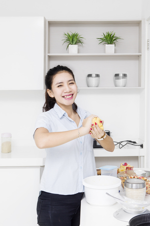masa: Smiling housewife cooking apple pie with dough in her hands while smiling in the kitchen