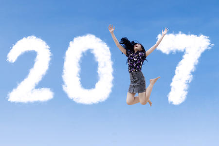 Concept of New Year 2017. Happy young businesswoman jumping on the sky with clouds shaped number 2017