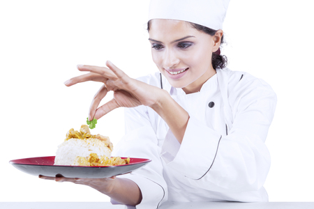 indian cookery: Image of a young Indian chef preparing a dish of yummy food while putting parsley in the studio