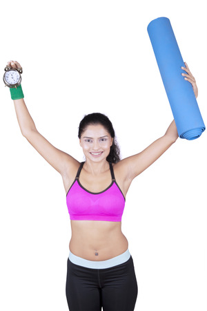 Portrait of young woman lifting a mat and watch while standing in the studio, isolated on white background Stock Photo