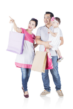Full length of smiling family shopping together while pointing something isolated on white background