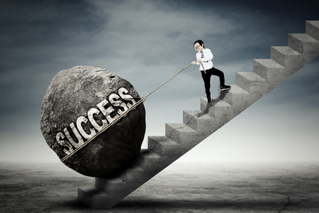 upward struggle: Image of a little businessman pulling upward a big stone with success word on the stairs Stock Photo