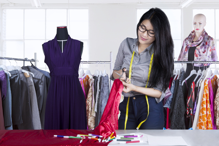 Portrait of fashion designer cutting material fabric by using a scissor while standing in workplace