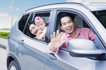 Portrait de famille heureuse regardant par la fenêtre de la voiture tout en souriant à la caméra sur l'autoroute