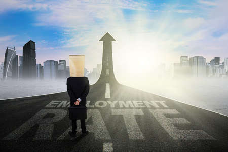 road to recovery: Image of businessman with cardboard head, standing on the road shaped upward arrow with employment rate text