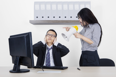 displeased businessman: Young female employee is screaming at her manager through megaphone while working with a computer in the office room Stock Photo