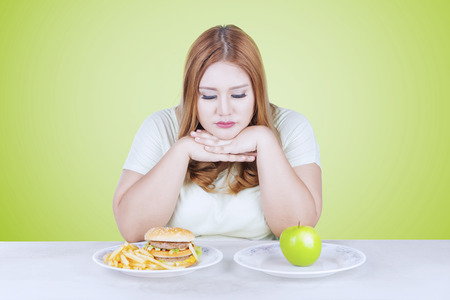 Overgewicht vrouw kijkt in de war, op zoek naar een frisse appel fruit en hamburger op de tafel Stockfoto