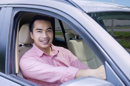 Portret van jonge zakenman besturen van een auto terwijl het glimlachen naar de camera in de snelweg Stockfoto
