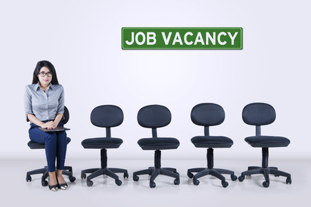 nervousness: Image of young female feeling nervousness and holding a clipboard while sitting on the chair with text of job vacancy and empty chairs in the hall