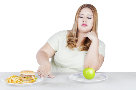 Photo of a blonde woman with overweight body refusing a plate of hamburger on the table