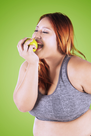 Photo of a blonde woman with overweight body, wearing sportswear and eating a fresh apple in the studio Stock Photo