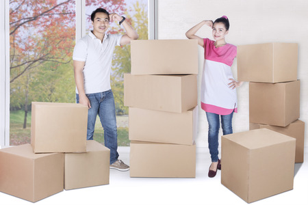 Full length of young man and woman standing besides pile of boxes with autumn background on the window