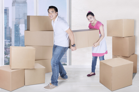 unfurnished: Full length of young woman and man carry box together in new apartment while looking at the camera