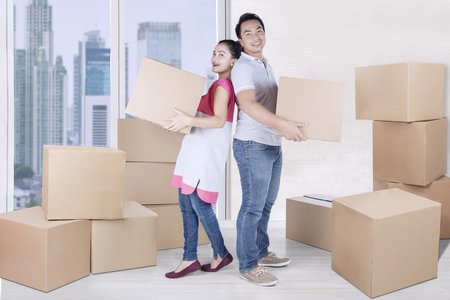 Full length of cheerful woman and man carry box together while standing in new apartment