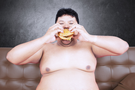 voracious: Image of greedy fat man sitting on the brown sofa while eating delicious hamburger