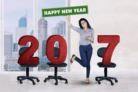 Young businesswoman standing with number 2017 on the chair while holding a smartphone at office Stock Photo