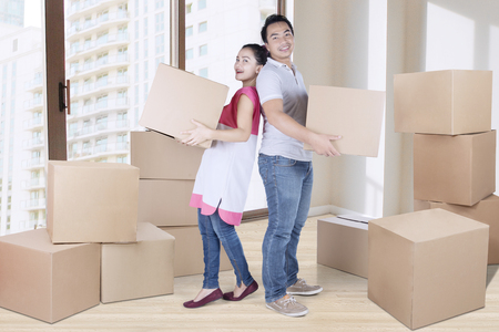 Full length of young couple carrying box together while standing in new apartment Stock Photo