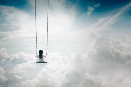 oscillate: Behind view of lonely child swinging on the sky and above the clouds