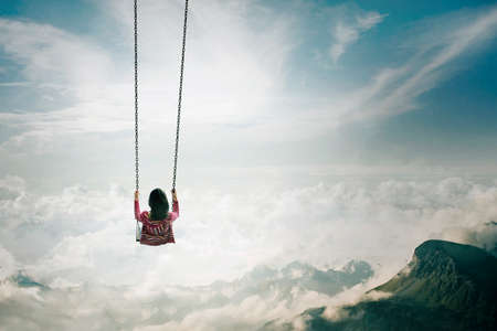 oscillate: Back view of young woman swinging above the clouds and the mountain Stock Photo