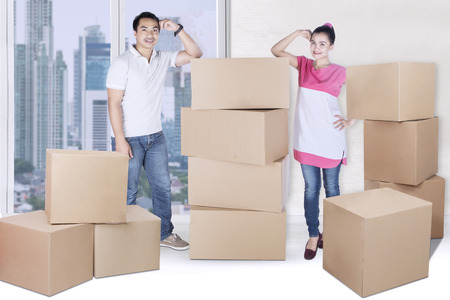 Full length of young wife and husband looking at the camera while standing with pile of boxes in new apartment
