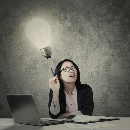 Empresaria asiática joven que tiene una idea con una bombilla brillante mientras se trabaja con el ordenador portátil y el papeleo en el escritorio