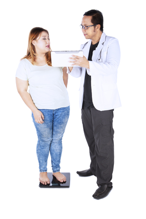 Full length of young male doctor measuring the weight of his patient while explaining a test result on digital tablet, isolated on white background