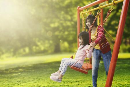 Retrato de la pequeña hija y madre que juega el oscilación en el parque mientras que sonríe junto Foto de archivo - 70562173