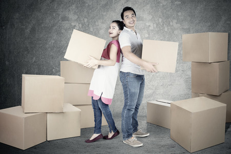 young wife: Full length of young man and wife holding box together while looking at the camera