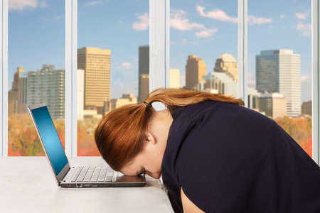 resting: Female entrepreneur feels sleepy and looks tired on a laptop with autumn background on the window
