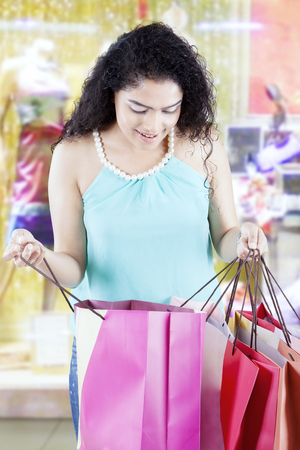 Portrait of beautiful woman checking into a shopping bag while standing in the fashion boutique Stock Photo