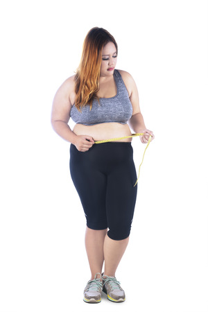 loose hair: Full length of overweight woman measures her belly while standing in the studio