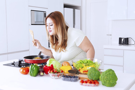 vegetable salad: Portrait of fat beautiful woman is cooking in the kitchen while sniffing meal on the frying pan, shot in the kitchen