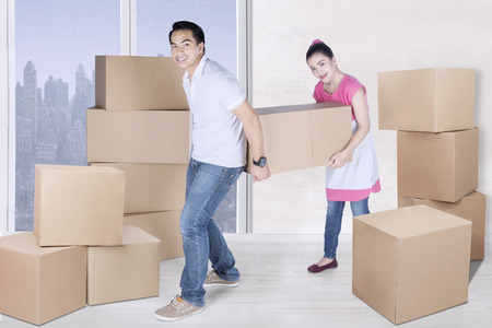 Full length of smiling man and woman carrying box together with winter background on the window Stock Photo