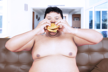 Voracious obese man eating a hamburger while sitting on the brown couch with shirtless at home