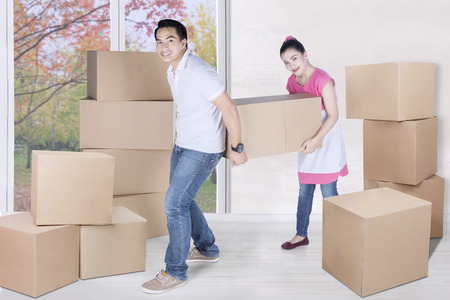 young wife: Full length of young husband and wife carry box together with autumn background on the window